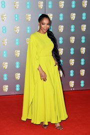 Naomi Ackie cut a vibrant figure in a caped chartreuse gown by Valentino at the 2020 EE British Academy Film Awards.
