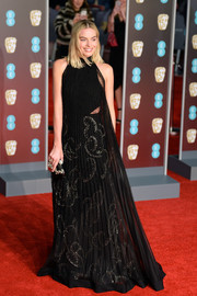 Margot Robbie went for edgy glamour in a black Givenchy Couture lace halter gown with a cutout underlay at the EE British Academy Film Awards.
