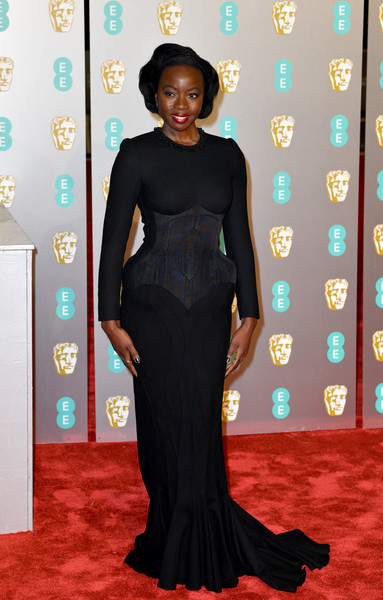 Danai Gurira attended the EE British Academy Film Awards wearing a figure-hugging black gown by Thom Browne.