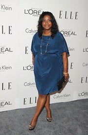 Octavia Spencer teamed her flattering blue shift dress with a black clutch with a gold clasp.