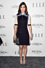 Lizzy Caplan topped off her ensemble with an elegant gray snakeskin clutch.