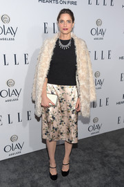 Amanda Peet styled her look with a simple white box clutch.