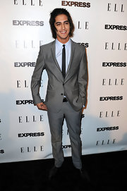 Avan looks retro fab in a skinny cut gray suit with black piped lapels.