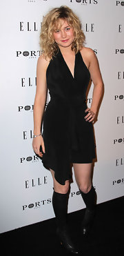 Brie Larson paired her black halter cocktail dress with matching knee high leather boots.