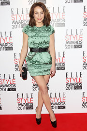 Noomi added a tough touch to her luxe dress with a black leather and chain link belt.