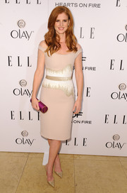 Sarah Rafferty added a hint of color to her look via a purple satin tube clutch.