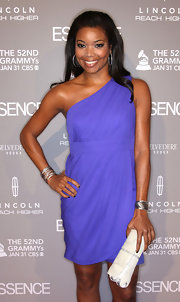 Gabrielle paired her one-shoulder dress with a white textured envelope clutch.