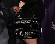 Kat Dennings paired her black cocktail dress with a patent leather tote bag.