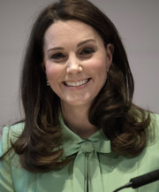 Kate Middleton framed her face with her signature side-parted style with curly ends for the Early Intervention for Children and Families Symposium.