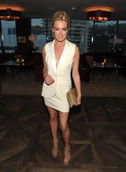 Cat Deeley accented her chic white skirt suit with a tan snakeskin envelope clutch.