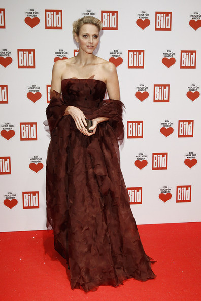 Princess Charlene looked magnificent in a strapless organza dress in a burnt red evening dress for the Ein Herz Fuer Kinder Charity Gala.