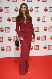 Nazan Eckes wore a wine evening dress with a deep-plunge and a centered zipper for the Ein Herz Fuer Kinder Charity Gala.