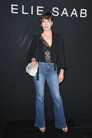 Milla Jovovich flashed a bit of skin in a black lace-panel blouse while attending the Elie Saab Couture show.