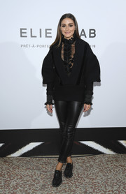Olivia Palermo teamed a black Elie Saab V-neck sweater with a ruffled lace blouse and leather pants for the brand's Spring 2019 show.