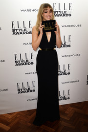 Suki Waterhouse looked svelte and sultry at the Elle Style Awards in a black evening dress with a plunging neckline and a gold belt.