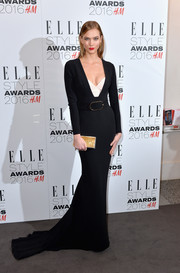 Karlie Kloss added a bit of shine with a gold box clutch by Jimmy Choo.