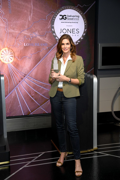 Cindy Crawford layered an olive-green blazer over a white button-down shirt for International Women's Day celebration at the Empire State Building.