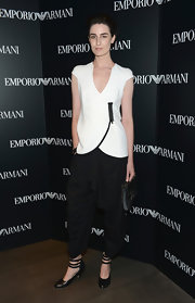 Erin O'Connor attended the Emporio Armani New York Flagship Opening wearing a white cap sleeve V-neck wrap top with a contrasting black zipper.