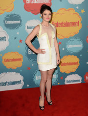 Emilie wore this stark white cocktail dress with a plunging mesh neckline, a laser-cut leather detail on the bust, and chic yellow trim.