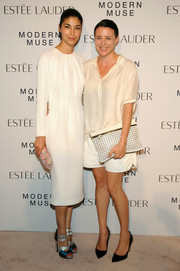 Garance Dore styled her white outfit with a chic patterned clutch.