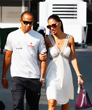 """Pussycat Doll"" lead singer, Nicole Scherzinger is seen wth race car driver Lewis Hamilton while looking all too classy in her v-neck white dress and purple ""Epi Alma Tote""."