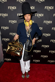 A metallic gold Fendi tote added major shine to Erykah Badu's look.