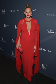 Chrissy Teigen complemented her gown with a red tube clutch by Rodo.