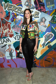 Kaya Scodelario gave her black pants some graphic appeal with a vintage Versace print jacket.