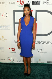Naomi Campbell flaunted her supermodel figure in a form-fitting royal-blue dress with a plunging neckline and a fluted hem at the First Ladies Luncheon.