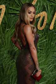 Rita Ora teamed a gold clutch with a partially sheer gown for the Fashion Awards 2017.
