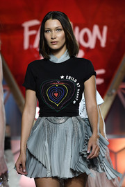 Bella Hadid layered a 'Child at Heart' T-shirt over a gray mini dress for her turn on the Fashion for Relief runway.