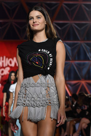 Isabeli Fontana walked the Fashion for Relief runway wearing a 'Child at Heart' tee with rolled-up sleeves and a knotted waist.