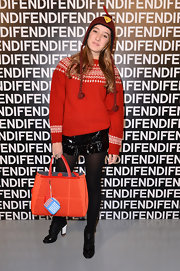 Leonetta Fendi mixed casual with dressy with shiny mini shorts and a bright red knit sweater at the Fendi runway show.