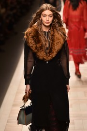 Gigi Hadid walked the Fendi runway carrying a chic fur-strap leather purse.