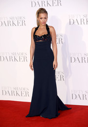 Rita Ora cut a curvy silhouette in a navy Miu Miu halter gown with an embellished neckline and a sexy slash just below the bustline during the UK premiere of 'Fifty Shades Darker.'
