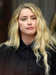 Amber Heard sported long blonde waves while talking to reporters at the Royal Courts of Justice.