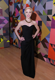 Katherine dons a floor length structured black evening dress with her short blond pixie cut.