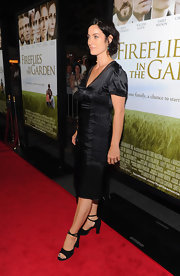 Carrie-Anne Moss topped off her black satin dress with black strappy heels.