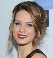To recreate Lyndsy Fonseca's lovely 'do, begin by sectioning out bangs and a few face-framing pieces. Next, backcomb hair through the crown and spritz with a little hairspray to add texture. Then, start to pull hair back and secure into a loose pony tail above the nape of the neck. To create Lyndsy's loose knot, twist and wrap the ponytail around the hair elastic and pin into place. To finish the style, curl the sectioned out pieces to create soft waves and ringlets and mist with a little hairspray.