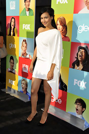 Naya Rivera added contrast to her asymmetrical white dress with black patent pumps.