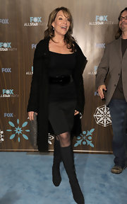 Katey Sagal wore black knee-high boots with her off-the-shoulder top, pencil skirt, and coat combo for an ultra-chic finish.