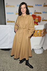 Debi wears an oversized tan trench with black boots for the Fraggle Rock Event.