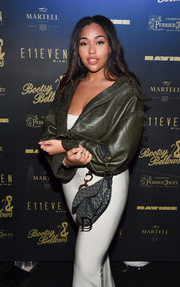 Jordyn Woods paired a dark green leather jacket with a sexy white skirt for the Big Game Weekend Experience.