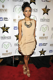 Katerina Graham paired her nude dress with a bronzed statement necklace.
