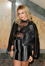 Tallia Storm hit the Julien Macdonald fashion show wearing a black leather biker jacket, sheer top, and mini skirt combo.