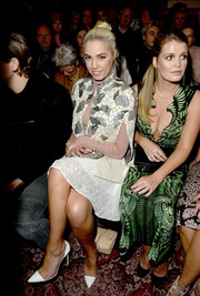 Amber Le Bon sat front row at the Julien Macdonald fashion show wearing an embellished cape and a lacy white skirt.