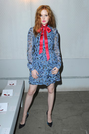 Ellie Bamber went the sweet route in a blue Erdem print dress adorned with a red satin bow when she attended the label's fashion show.