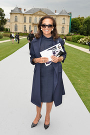 Giovanna Repossi layered a navy coat over a high-neck dress for the Dior Couture fashion show.