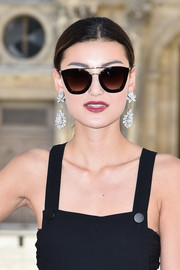 Amalie Gassmann attended the Dior fashion show wearing a pair of red carpet-worthy diamond chandelier earrings from the label.