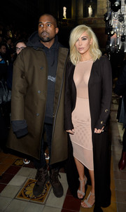 Kim Kardashian added a little modesty to her see-through net dress with a floor-length black Lanvin coat when she attended the label's fashion show.